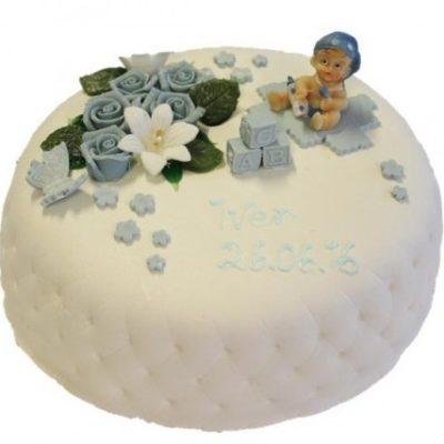 Marsipankake med blå blomsterpynt og figur av en baby